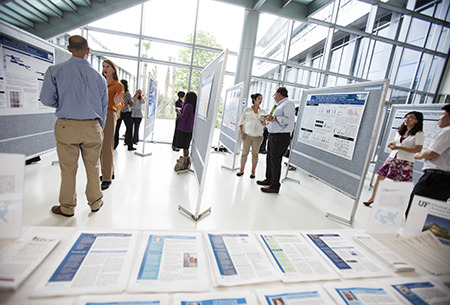 Students and faculty discuss their work at a poster session during CTSI Research Day 2013.
